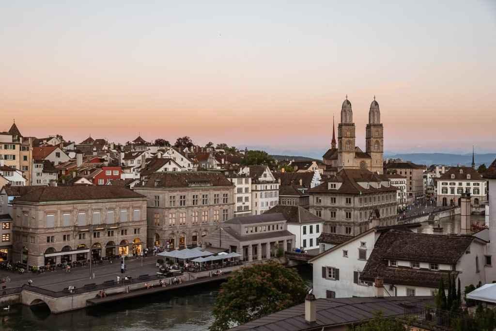 Sonnenuntergang in Zürich mit Großfrauenmünster und den Alpen im Hintergrund