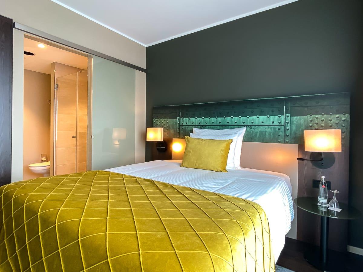 Blick ins Superior Zimmer - Bett & Eingang zum Badezimmer - im Leonardo Dortmund Hotel.