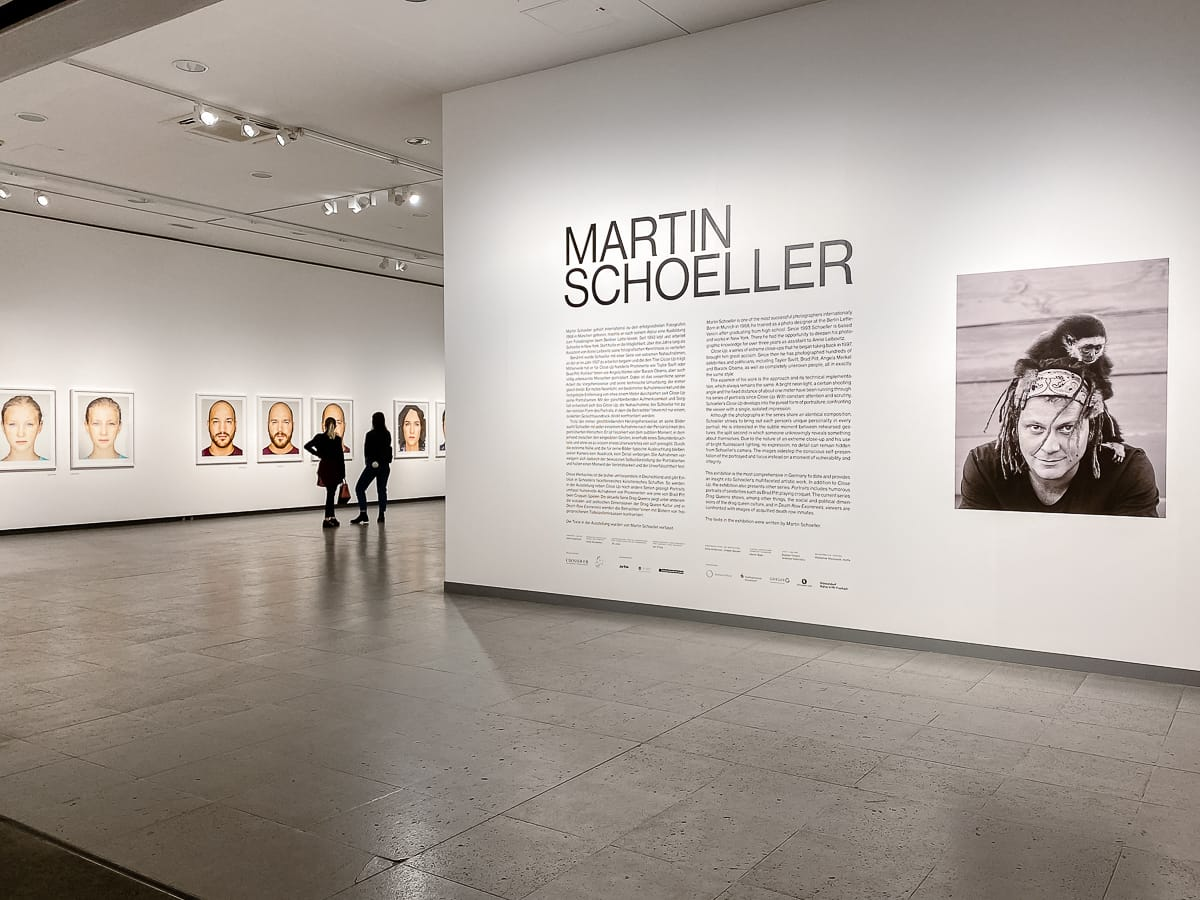 """Eingang zur Werkschau von Martin Schoeller im NRW-Forum. Blick auf sein Foto und Biografie, dahinter die Serie """"Identicals"""" mit zwei Besuchern."""