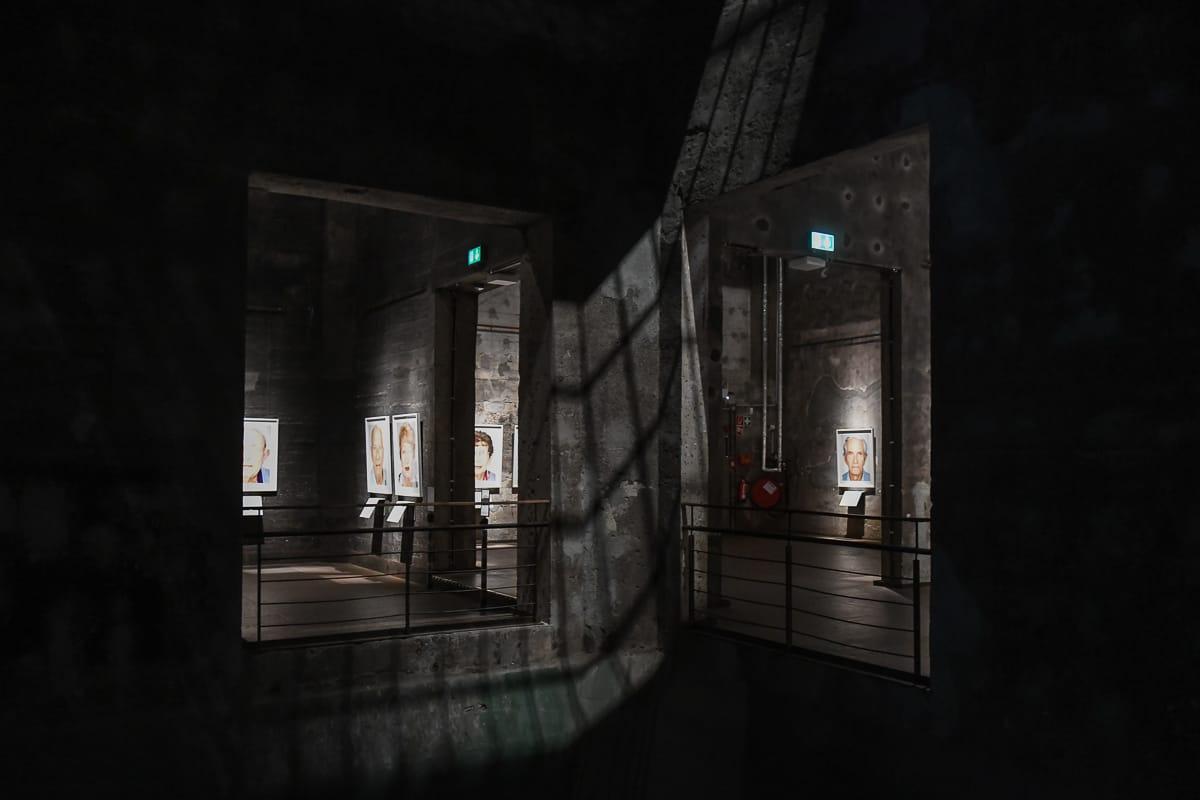 """Im Inneren der Kohlemischanlage - dunkel, schwarze Wände und Schächte und daran """"Survivors""""."""
