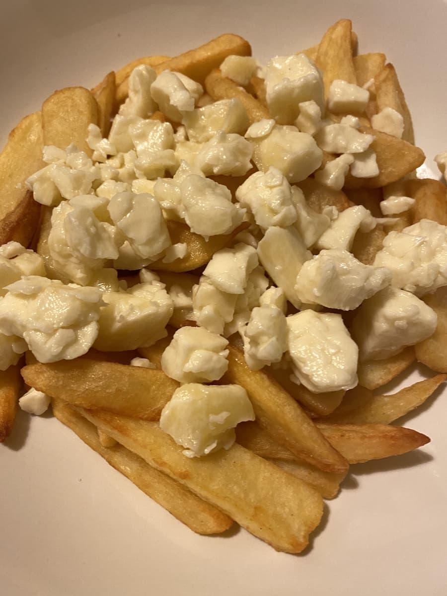 Cheese Curds drappiert auf frisch frittierten Pommes.