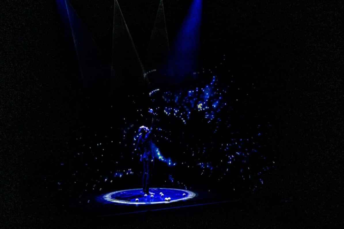 Pavel Roujilo am Anfang seiner Jonglage mit einer multimedialen Milchstraße auf einem fast durchsichtigen Vorhang