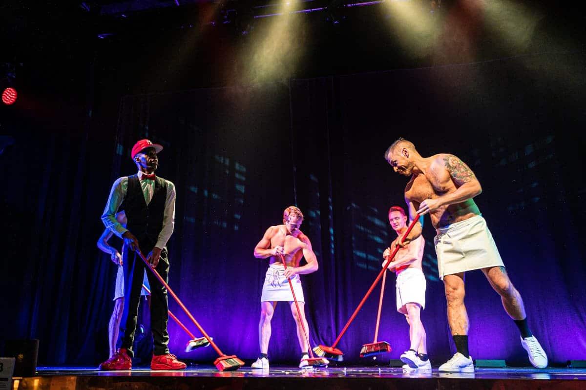 Die Wild Boys putzen die Bühne mit Besen, dazu bis auf P.Fly leicht bekleidet mit einem Handtuch.