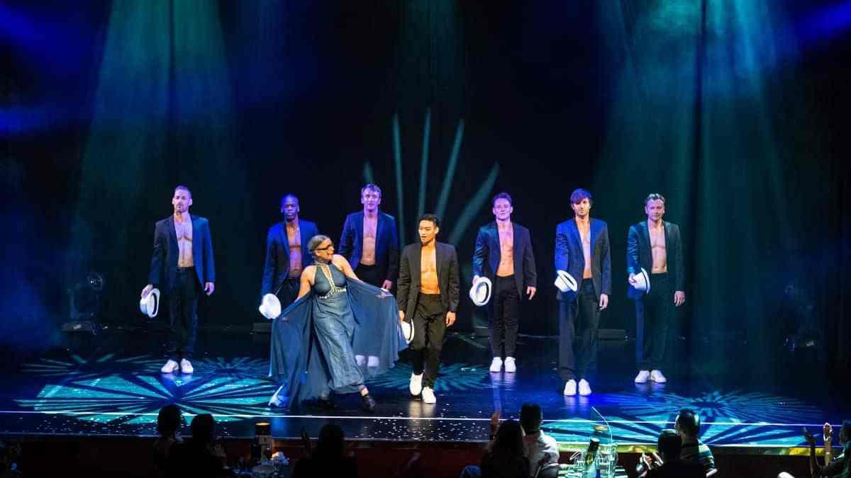 Rosemie und die Wild Boys auf der Bühne am Ende der Show. Die Herren im Sakko, Oberkörper darunter frei, Hut in der Hand. Rosemie in einem blauen, langen Abendkleid.
