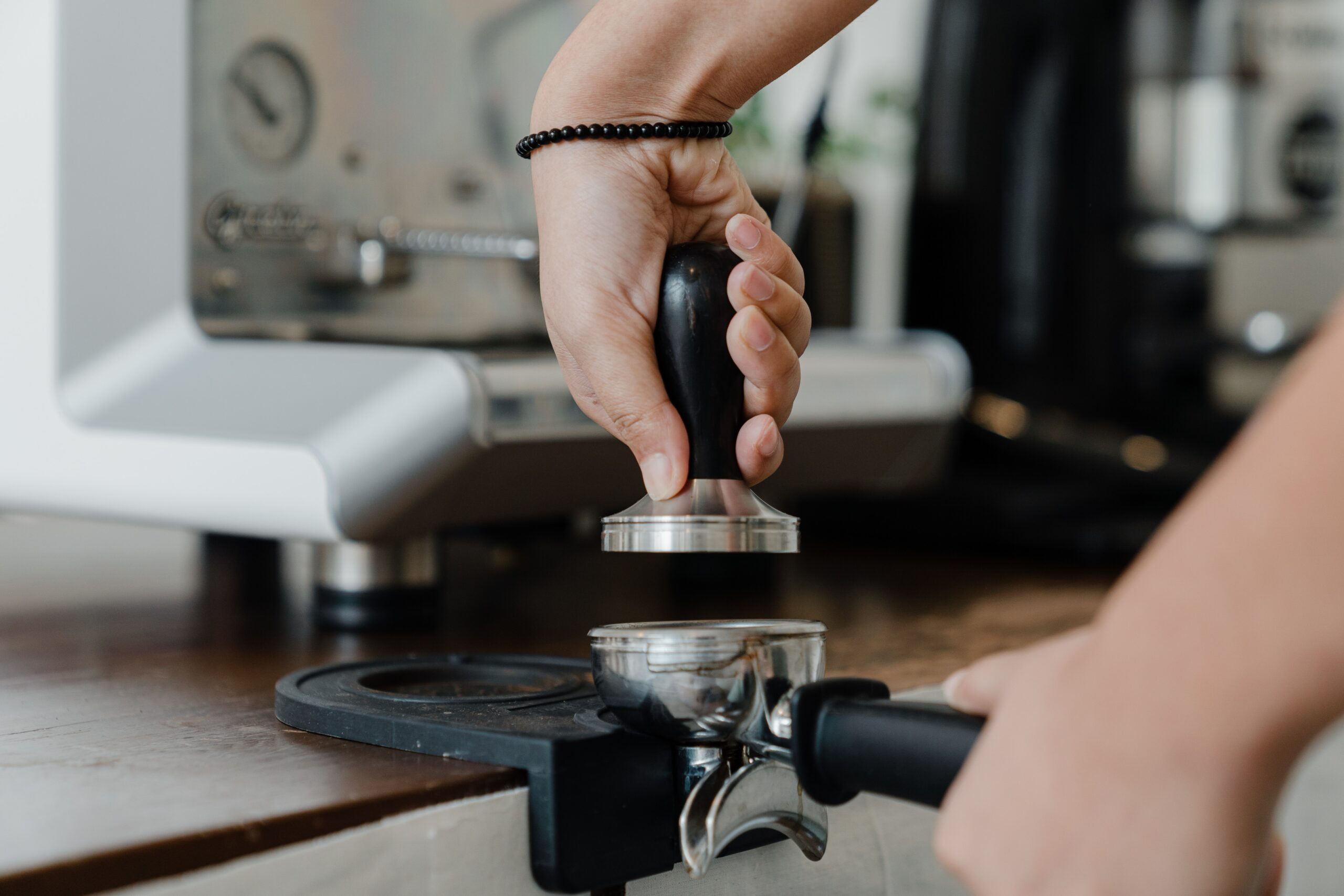 Person tamping ground coffee for an espresso machine