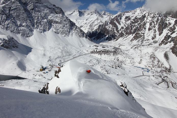 Snowboarding steep chutes above Roca Jack at Portillo