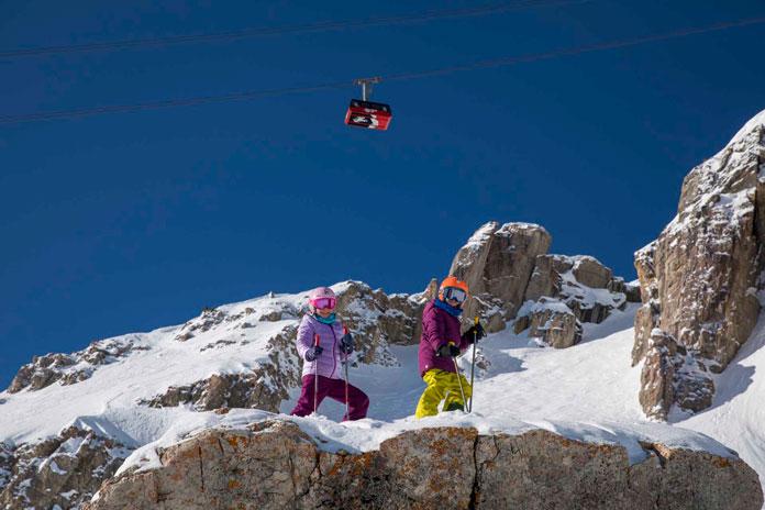 Kids skiing under the iconic Tram at Jackson Hole