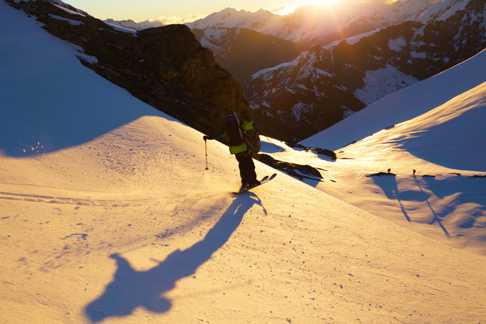Craig Murray skiing down Mt Aspiring toward Bevan Col at sunset