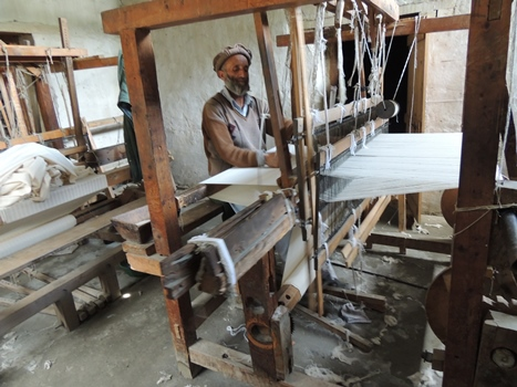 a local man weaves the cloth for the embroidered napkins sold through the Snow Leopard Trust webstore