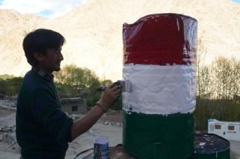SLC-IT employee Chosphel paints a steel barrel for re-use.
