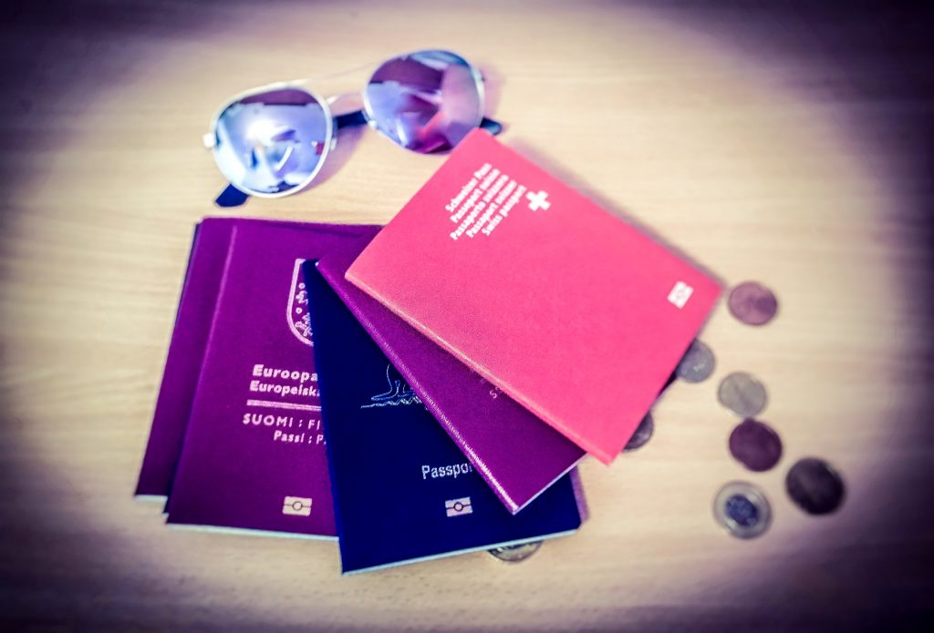 Swiss passport, finnish passport, Australian passport, mirrored sunglasses and coins on wood