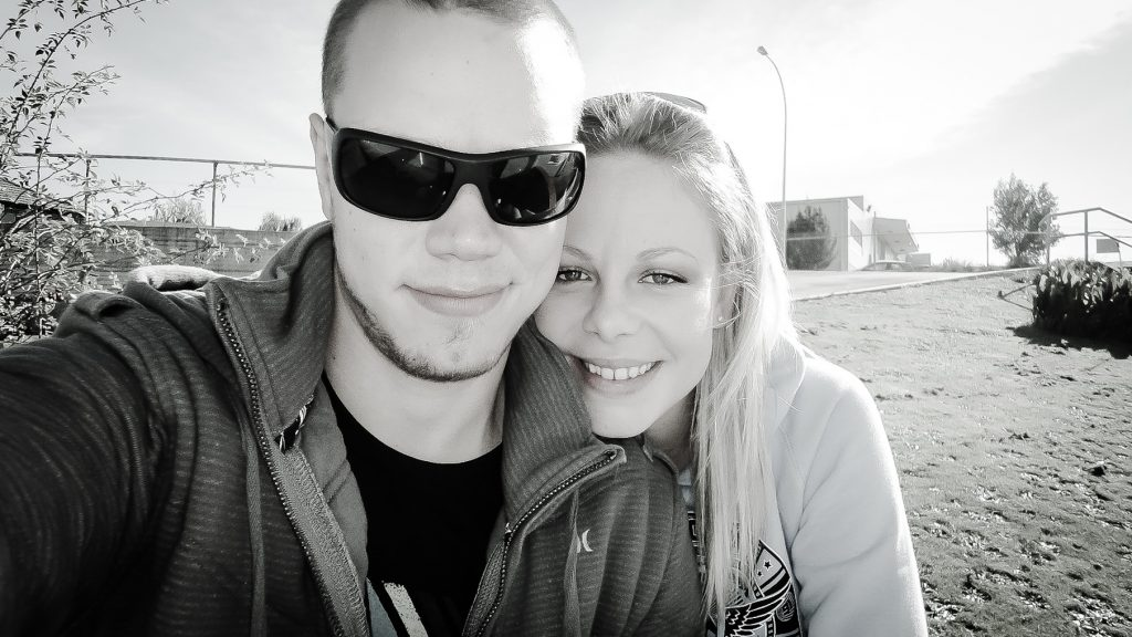 photo of couple sitting outside at a hostel. Man has sunglasses and in black and white