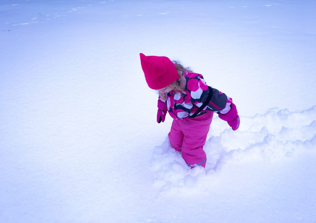 Girl playing in the snow in Finland wearing winter clothes. Lots of snow