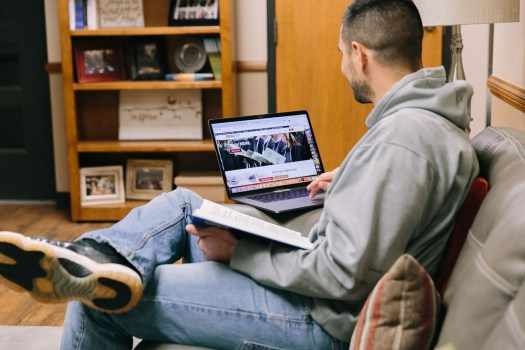 Adult Student sitting on couch w laptop