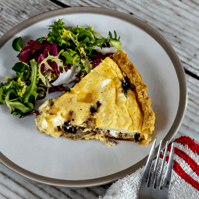 slice of quiche on a plate with salad
