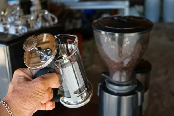 Woman holding French Press coffee maker in front of coffee bean grinder