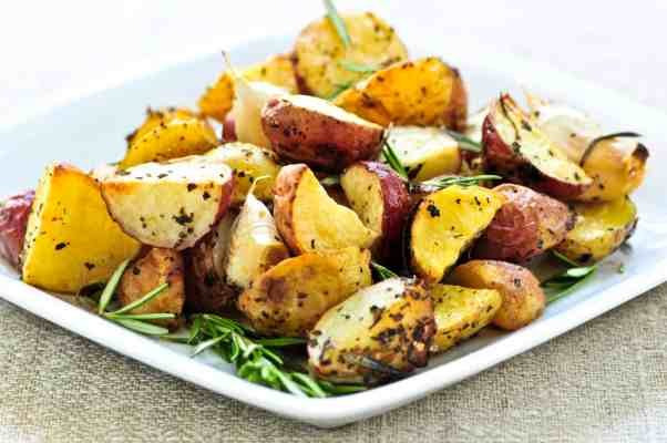 White plate with 3 ingredient onion roasted potatoes garnished with rosemary sprigs
