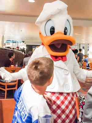 Non descript boy leaning in for a hug from Donald Duck at Chef Mickey Disney World