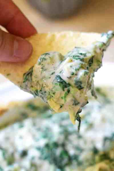 Tortilla chip dipped in 3 ingredient spinach and artichoke dip being held by a non-descript hand