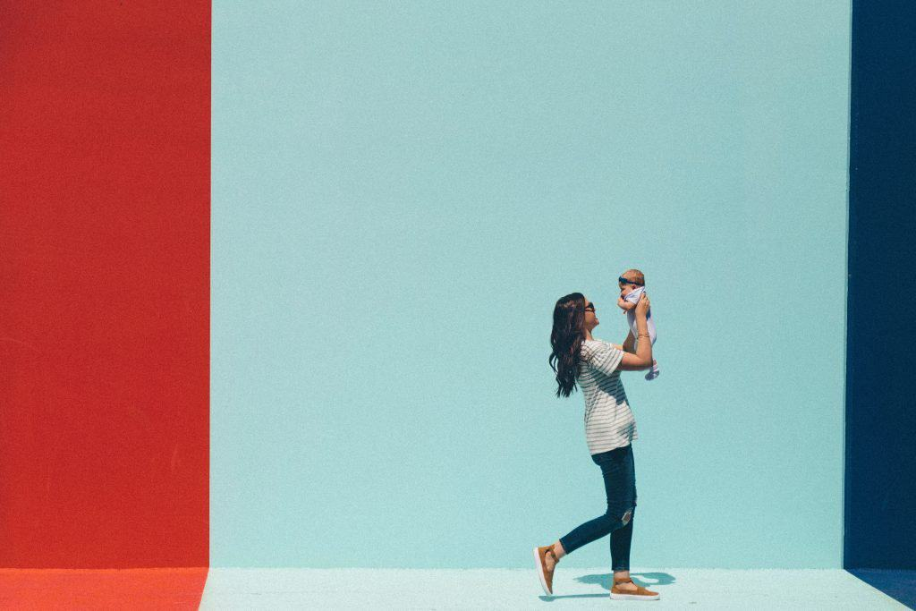 mom with baby in front of colorful wall