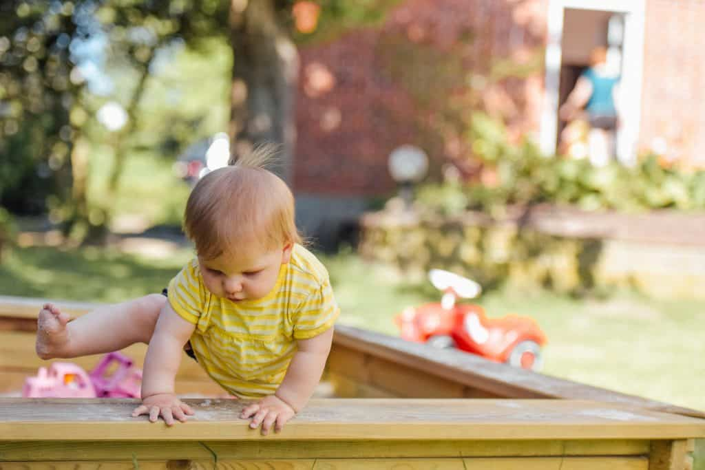 baby climbing out of sandbox