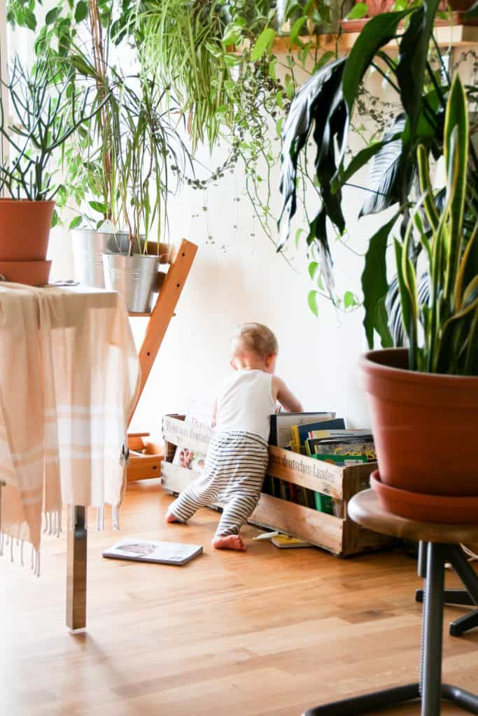 baby leaning on books with plants all around