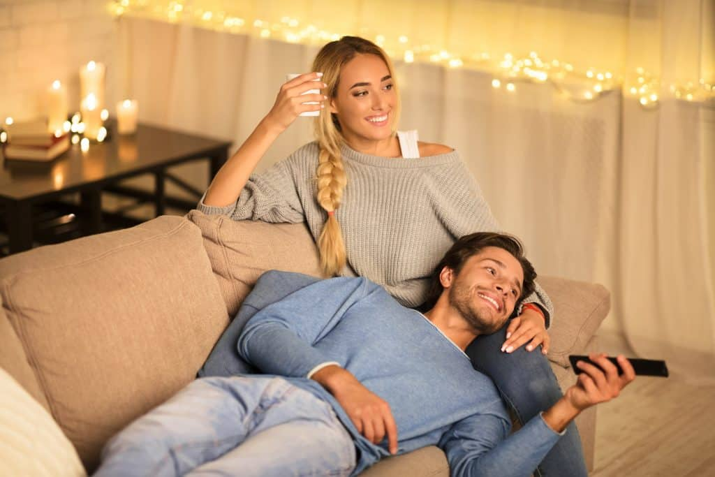 Cute couple watching tv in cozy home atmosphere
