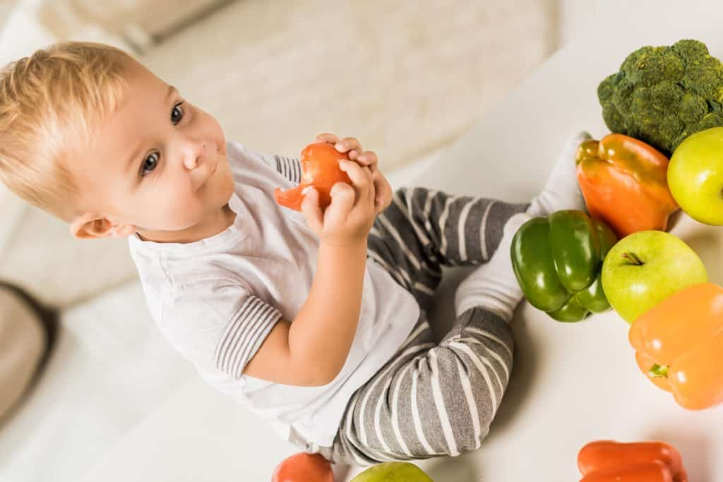 Toddler holding vegetables