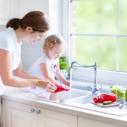 Toddler and mom cleaning vegetables