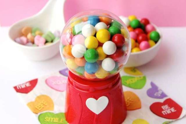 Need valentine crafts ideas for easy DIY valentines for kids? This DIY mini gumball machine is the perfect Valentine for your little mini me's! Kids absolutely love these replica gumball machines filled with multi-colored gumballs or Valentine's day candy. Plus these valentines for kids are simple and easy to make. Learn how to make this easy DIY Valentine's day craft for kids. Plus explore other ideas for easy DIY Valentines for kids along with free printable valentines for your creations.