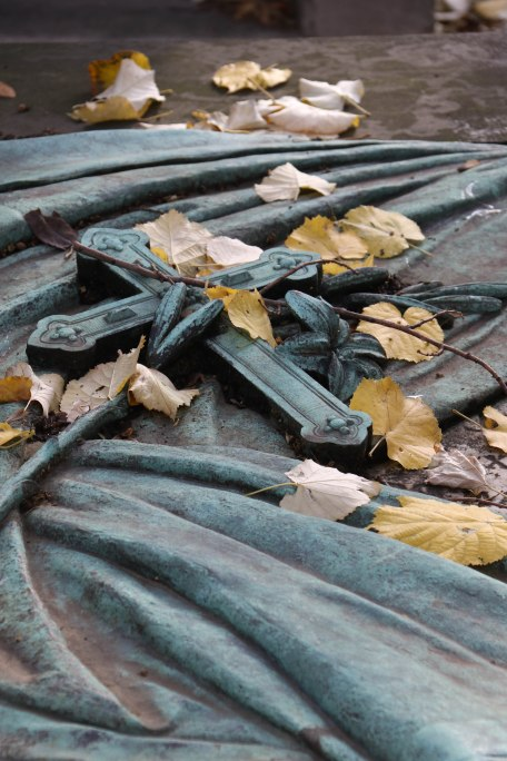 Cross and fallen leaves. Père Lachaise. Copyright Fiona Michie.