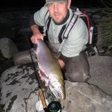 Angler holding silver salmon hooked on fly gear.