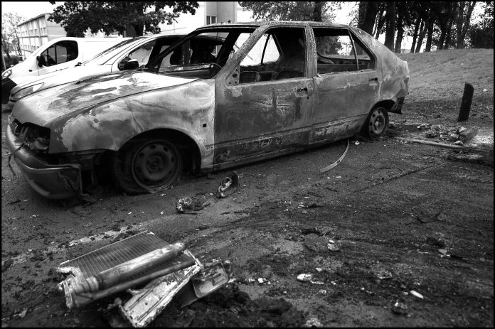 Remains of burnt car (Renault 19) during French riots 13 November 2005. Source:Flickr. Photo: Alain Bachellier. (CC BY-SA 2.0)