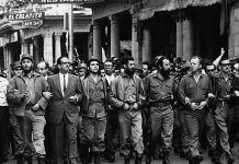 Photo was taken on March 5, 1960, in Havana, Cuba, at a memorial service march for victims of the La Coubre explosion. On the far left of the photo is Fidel Castro, while in the center is Che Guevara, on the right : William Alexander Morgan and Eloy Gutiérrez Menoyo. Source: Museo Che Guevara (Centro de Estudios Che Guevara en La Habana, Cuba). Photo: ukendt. Public Domain.