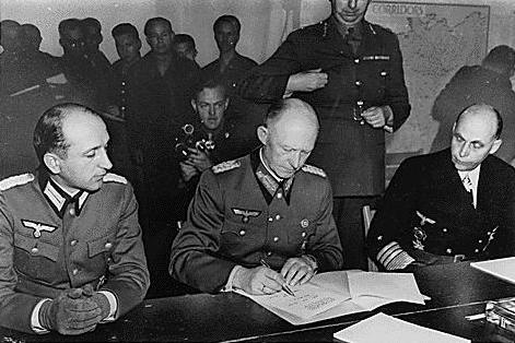 Alfred Jodl (between Major Wilhelm Oxenius to the left and admiral (Generaladmiral) Hans-Georg von Friedeburg to the right) signing the German unconditional surrender at Reims, France on 7 May 1945. Item from Collection FDR-PHOCO: Franklin D. Roosevelt Library Public Domain Photographs, 1882 - 1962 (List). Public Domain.