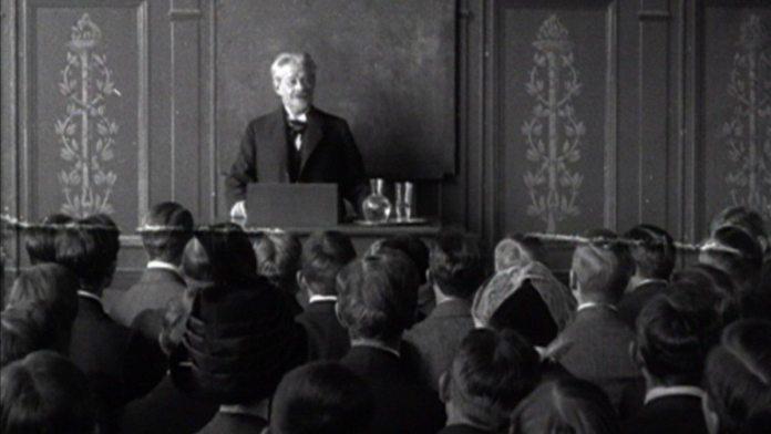 Professor George Brandes (1842-1927) holder forelæsning på Københavns Universitet. De studerende rejser sig høfligt før og efter forelæsningen. Fra en 1 minut lang stumfilm fra 1912 (http://filmcentralen.dk/museum/danmark-paa-film/film/professor-georg-brandes-paa-universitetets-katheder)