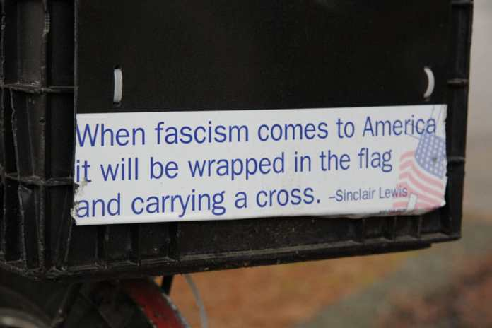 """Closeup of bumper sticker with famous Sinclair Lewis line """"When fascism comes to America it will be wrapped in the flag and carrying a cross"""" This quote is often attributed to Sinclair Lewis but has not been verified. The Sinclair Lewis Society notes the following: This quote sounds like something Sinclair Lewis might have said or written, but we've never been able to find this exact quote. Date: 27 November 2008. Source: Own work. Author: Robert F. W. Whitlock from Olympia, Washington. (CC BY 2.0)"""