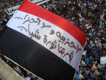 """Masdar Online. Student protestors in Taiz are fed up with politics of the old parties in Yemen, so on this Yemeni flag they wrote: """"No partisanship! And no parties! Our revolution is a revolution of youth"""""""