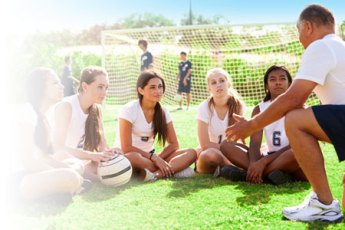 Girls youth soccer team sitting on the field and listening to their coach