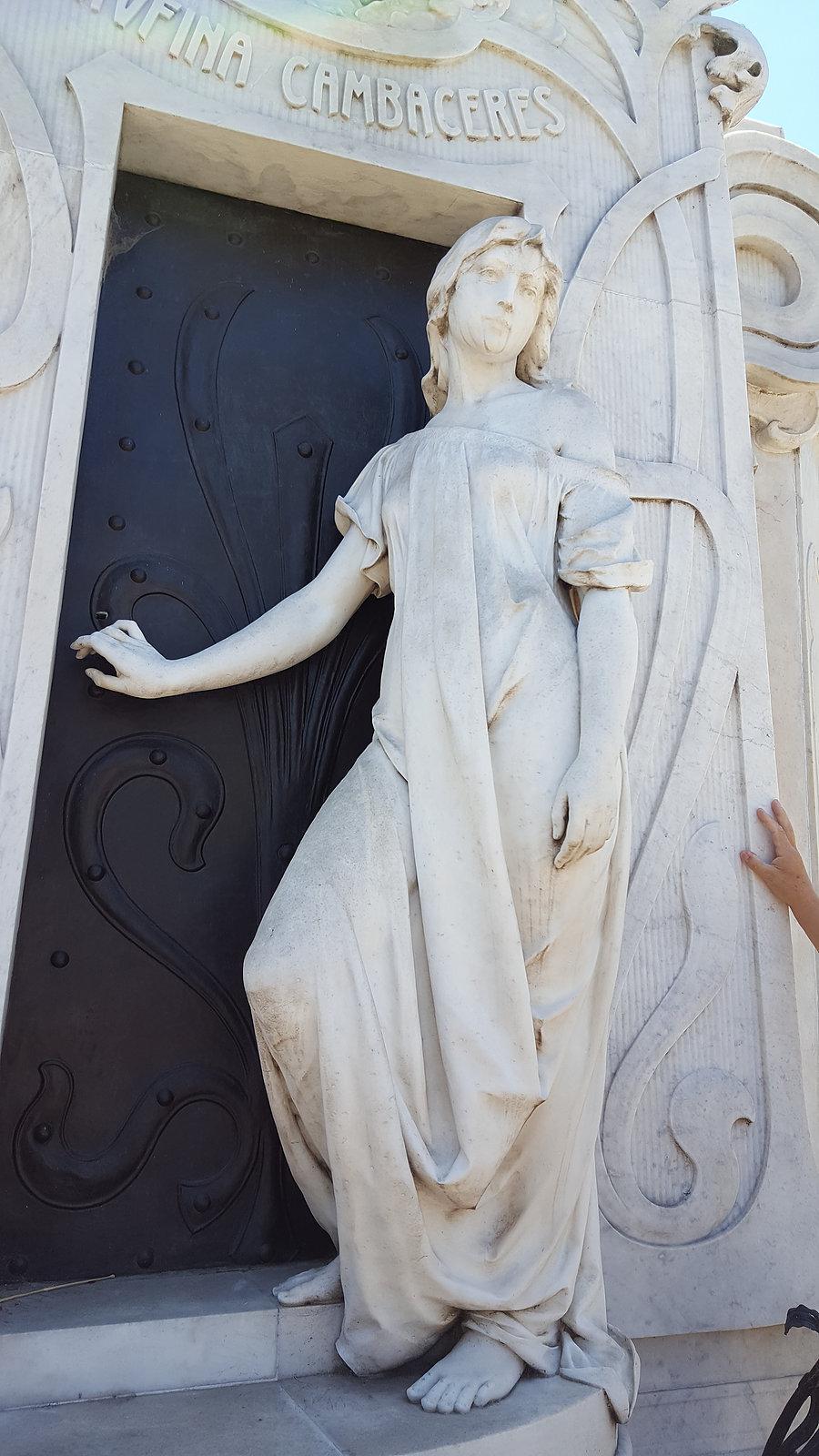 Tombe de Rufina Cambaceres_ photo de Rémy Jeune fille de 19 ans enterrée vivante par erreur suite à une crise d'apoplexie le jour de son anniversaire. Sa mère fit rouvrir sa tombe et constata qu'elle avait essayé de se libérer. Suite à cet incident, on décida d'accrocher une ficelle reliée à une cloche au poignet des personnes enterrées. Elle est représentée ici sortant de sa tombe car la légende dit que son fantôme se promène dans le cimetière et dans la ville de Buenos Aires. Elle est surnommée la dame blanche.