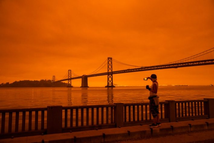 A woman takes in the view from the Embarcadero as smoke from various wildfires blankets San Francisco in darkness and an orange glow on 9 September 2020