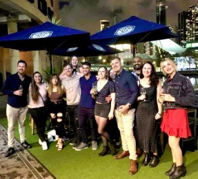 group of guys and girls standing for photo while enjoying drinks by the water at a social event in the city