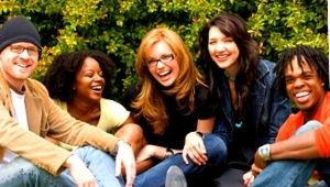 group of five adults meeting in a park while smiling and sitting down behind green bushes