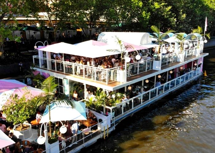 white arbour afloat with palm trees floating full bar on yarra river in victoria's cbd