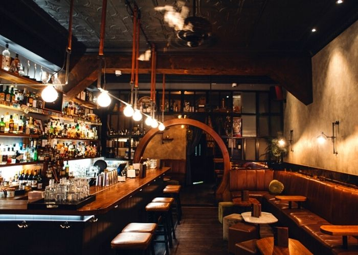 dimly lit interior of fitzroy bar the black pearl with leather booths, bar stools and spirit bottles on shelves