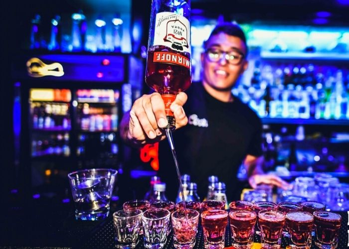 bar tender pouring Smirnoff shots in a blue neon lit nightclub bar