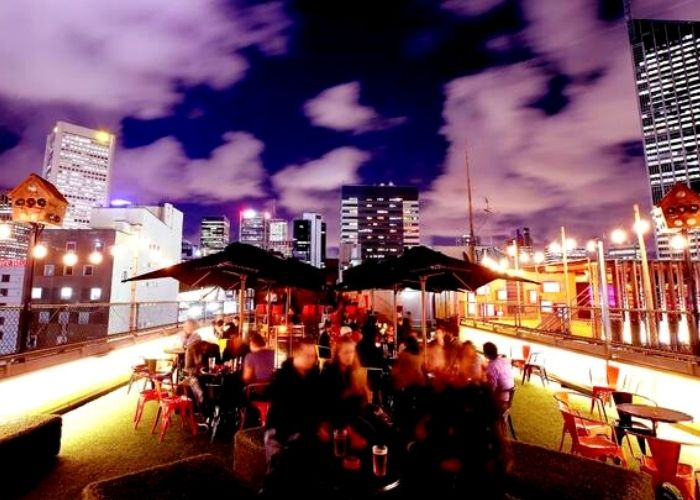 Group of people on top of curtin house roof top bar and cinema over looking city views