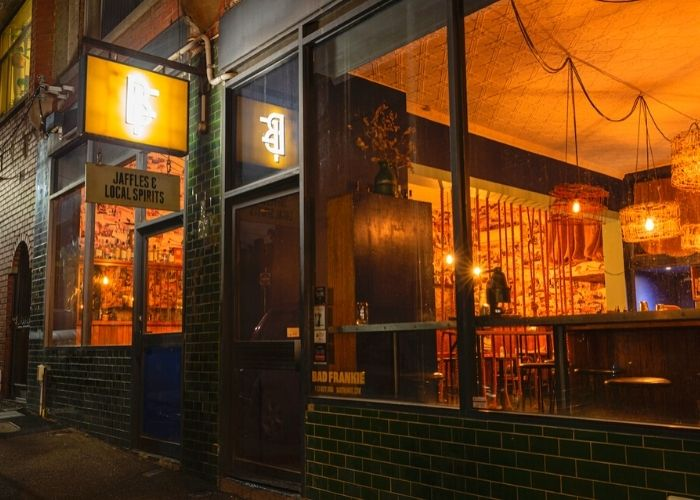 street view of bad frankie bar at night with lights glowing from greeves street Fitzroy