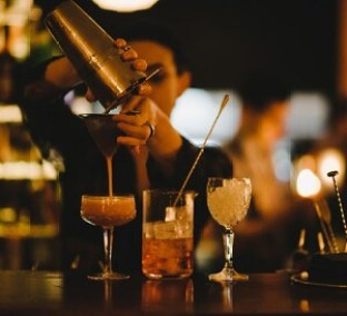 bar tender pouring cocktail through strainer with straw and wine glass