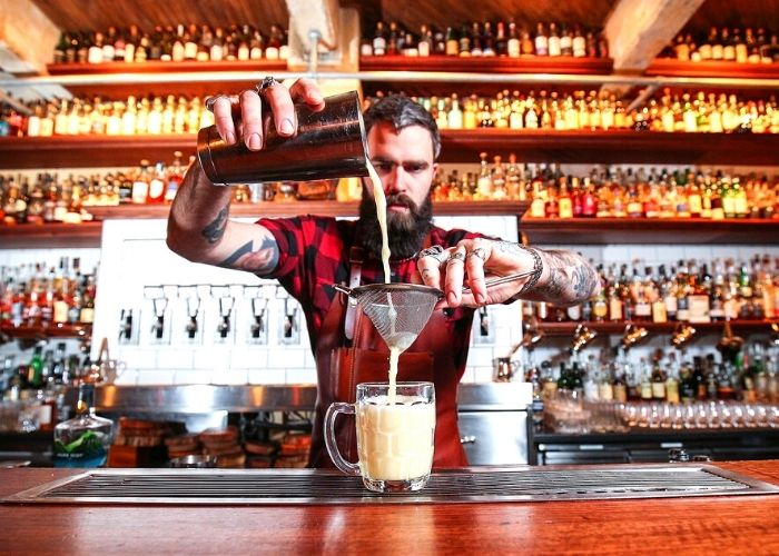 Bar tender with beard and tattoos pouring malt whisky on wooden bar with hundreds of whiskies in back ground shelves in Boilermaker house lonsdale street